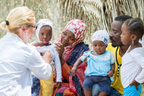 Nurse on medical mission trip to Africa examines family members.