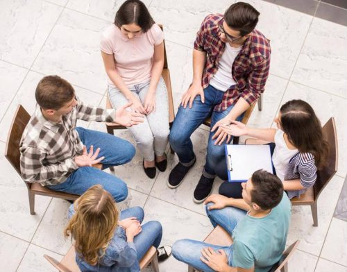 A clinical mental health counselor leads a group therapy session.