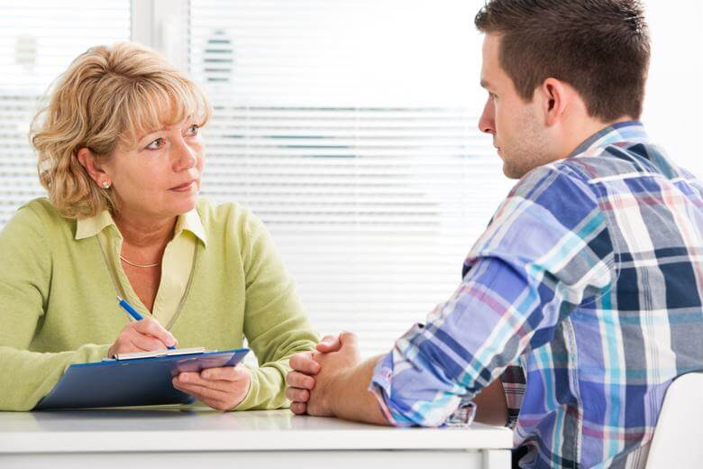 A rehabilitation counselor leads a client consultation.