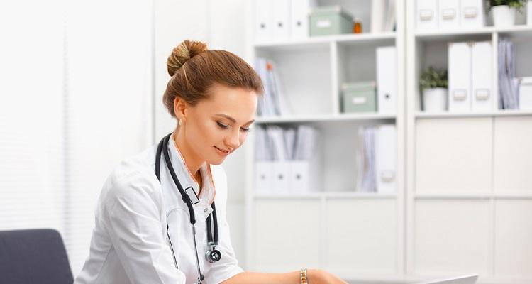 A nurse typing on a laptop.