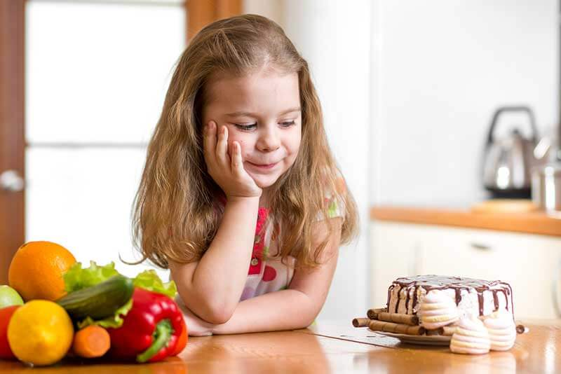 A young girl looking at a cake