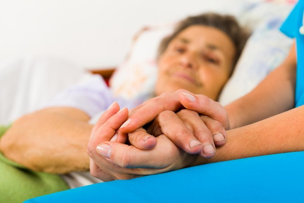A hospitalized, bedridden patient holds the hands of her social worker.