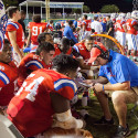 The John Curtis Varsity Football team wearing red uniforms with blue trim huddles up on the sideline with their coach as they plan the next possession