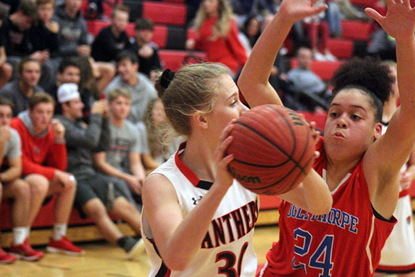 A player from the Jackson County Panthers Girls Basketball Team tries to find a clear pass around a defender