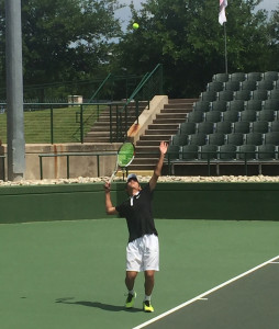 Justin Chen serves on center court in the regional final