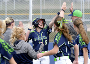 Ridgeline's Tyler Thornton (5) celebrates with players and coaches after hitting her second home run of the game against Sky View on Thursday.