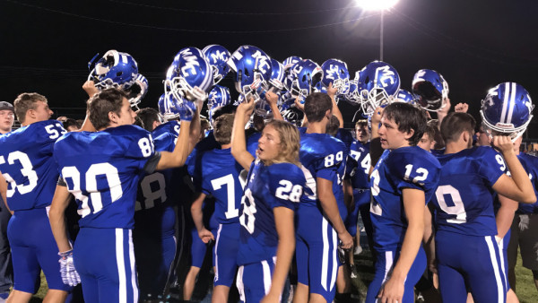 Players huddle following the Tigers' 28-26 victory over White House Heritage.