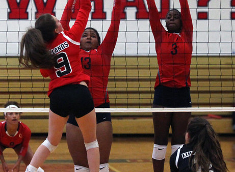 Firelands Emily Squires spikes the ball over Tiffani Burke and Nya Grady- Norman of Oberlin. Randy Meyers -- The Morning Journal