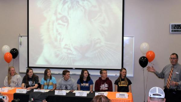 AD Tim Walker congratulates the athletes. Seated left to right: Ty Stiller, Michelle Rugh, Celeste Barron Nicoletti, Bradley Jackson, Erin Penn, Mitch Lugsch and Olivia Hogenkamp.