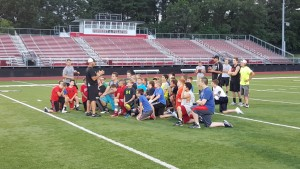 Youth Football Players taking instruction from Defensive Coordinator Coach Beaton