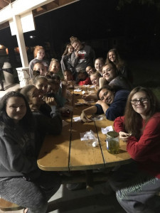 JV and varsity bonding at the camp fire while making s'mores