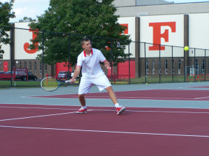 Sophomore No. 1 doubles player Adam Crawford slices a forehand return during warm-ups.
