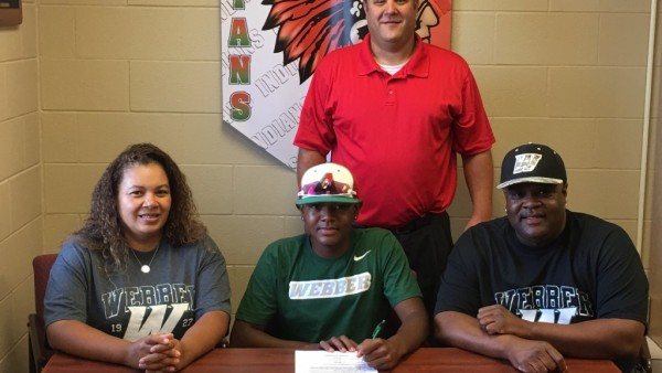 Brandon Johnson signs on to pitch at Webber International University as his parents, Porscha and Charles, and AHS coach, Adrian Heim, look on.