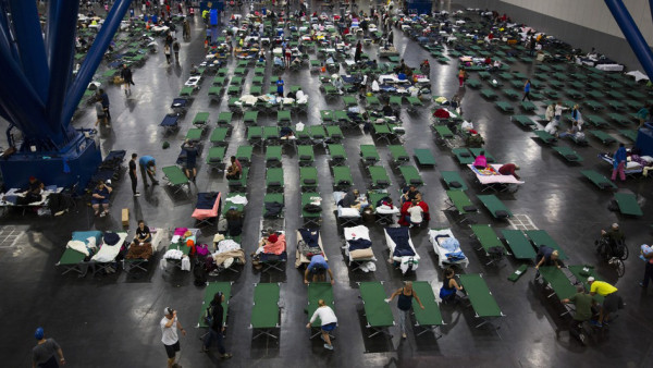 Evacuees fill up cots Monday at the George Brown Convention Center in Houston, which has been turned into a shelter run by the American Red Cross to house victims of the high water from Hurricane Harvey. Experts say it's best to donate money, not items or services, to trusted charitable organizations after a disaster — and to keep long-term needs in min