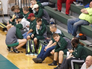 The coaches and the wrestlers sit anxiously, waiting for their turn.