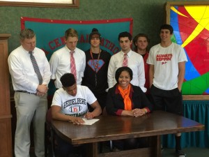 Senior Jamison Bradley signs his agreement to play football at Heidelberg. Looking on are members of the Football team, Coach Scott Palte and Bradley's mother, Lisa