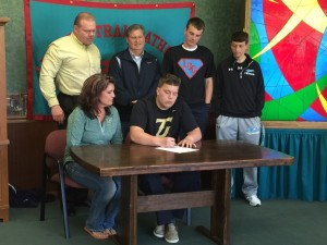Spencer Collins signs with Tiffin as his parents, teammates and coach Kevin Bruin look on.