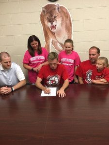 Trenton Signing with coach and family looking on!