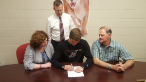 Coach Adams and Danny's parents look on as he signs.