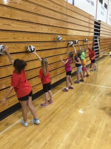 1st-3rd grade campers work on serving skills with wall traps.