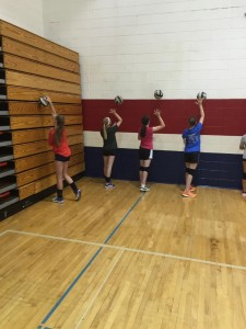 6th-8th grade campers work on serving skills with wall traps.