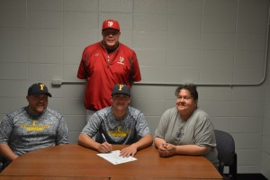 NPHS senior Zach Lovell signs his letter of commitment to Franklin College. With him are his older brother Jay Lovell and mother Pam Lovell and NPHS head coach Shawn Lyons.
