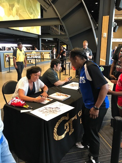 Coach Dana Smith gets an autograph from Coach Joseph