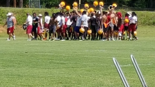 The Panthers gather around Coach Nickles for instruction before 7 on 7 drills.