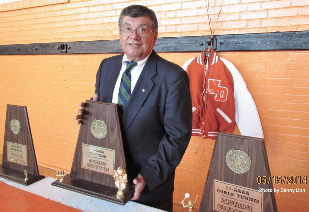 Ernest Cerda stands with some of the district titles his teams won in 2014. (Photo by Danny Linn)