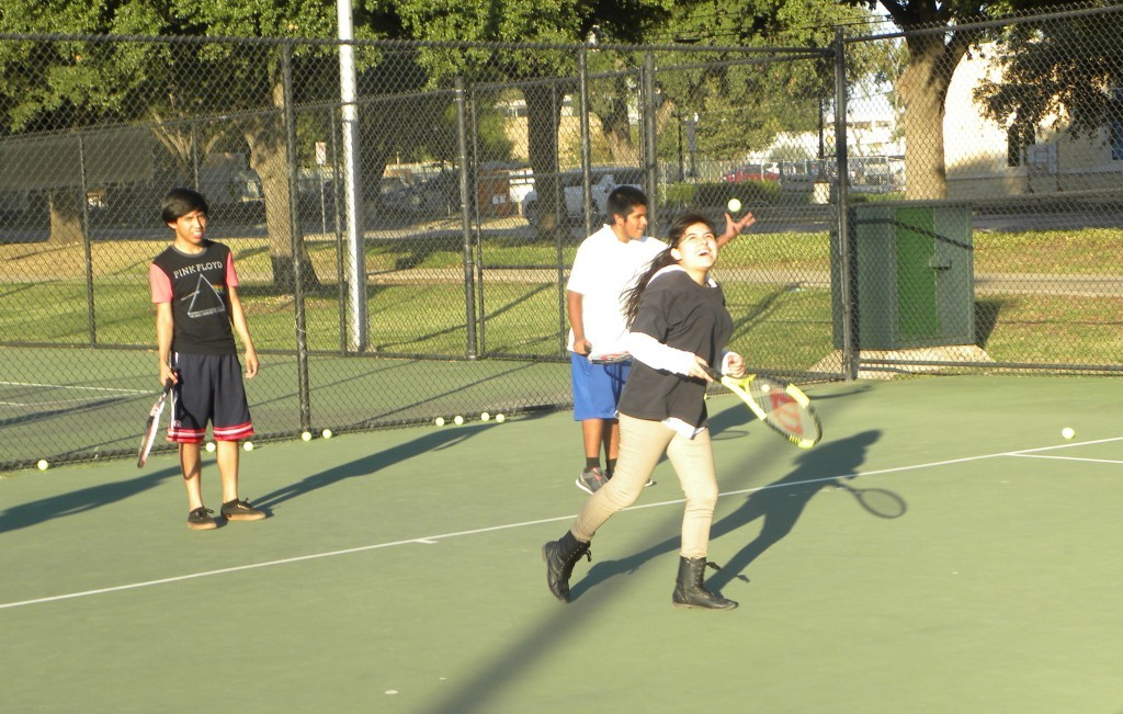 Angel Bazan watches her shot sail away as Mario Almaguer (left) and John Rodriguez-Olivos prepare to hit balls.