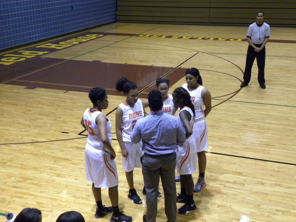 North Dallas girls basketball coach Erik Grayson talks to his starters during a timeout.
