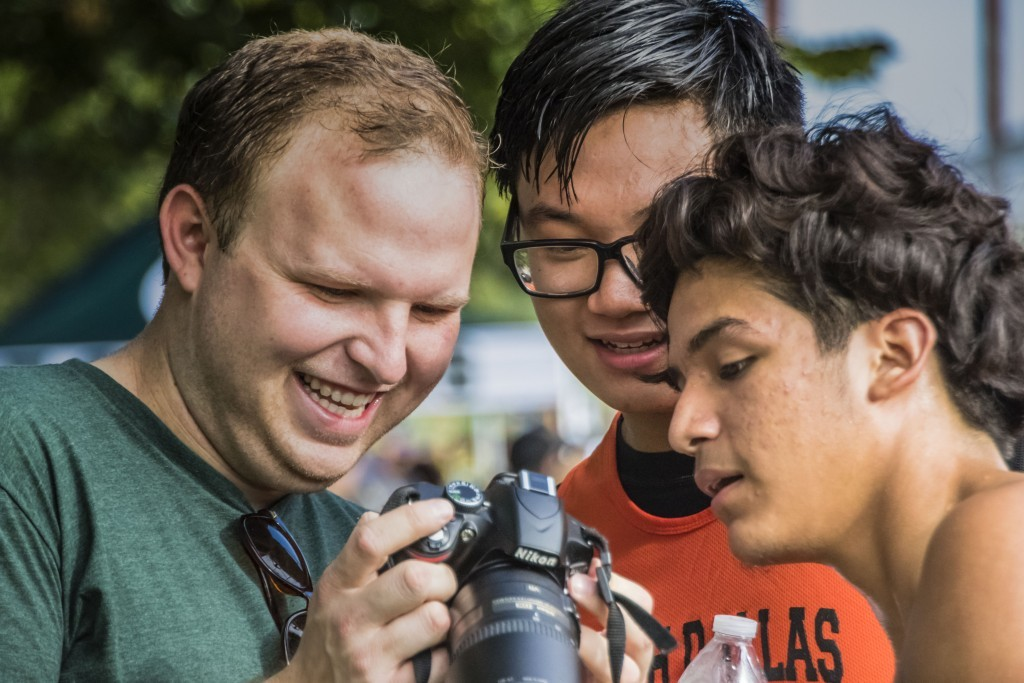 Economics teacher Ryan Davenport (left), Steven Do and Leo Campos check the camera.