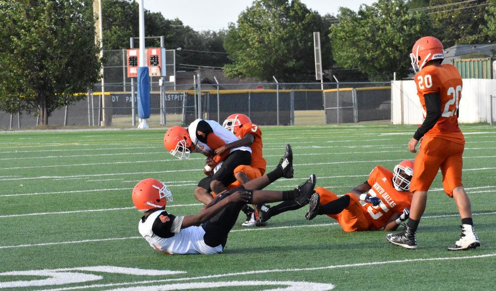 North Dallas receiver Christian Armstrong (1) is wrestled to the ground after making a catch.