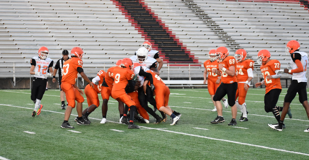 The Orange defense converges on a White ball carrier. The defense won the game.