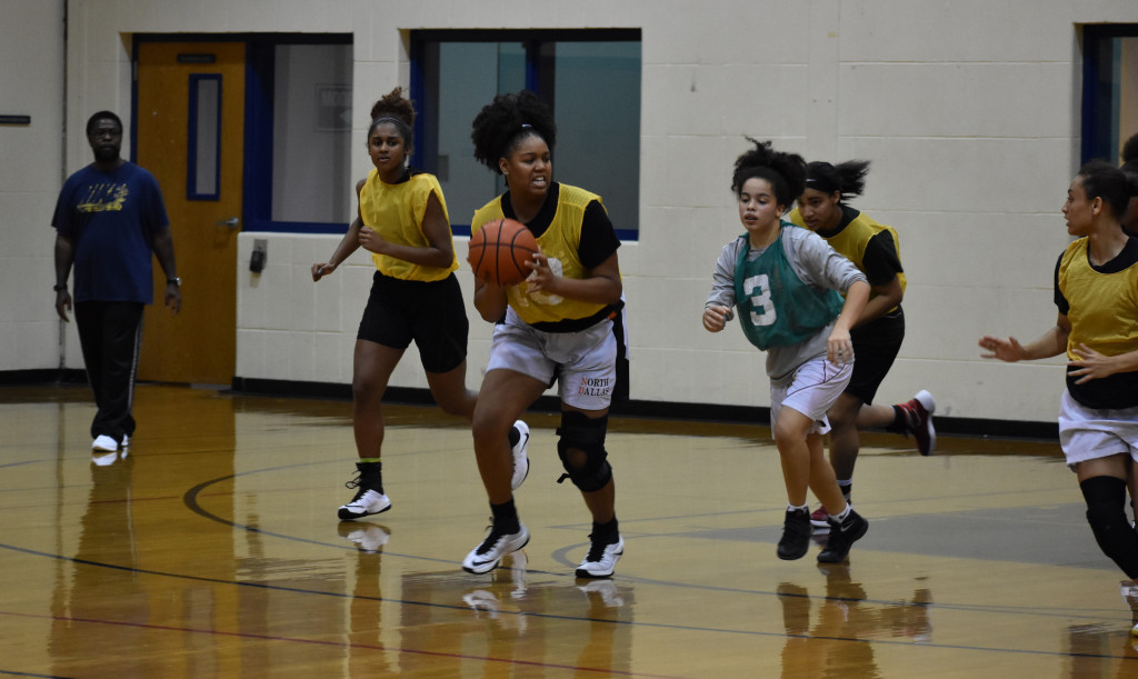 During grabbing a loose ball, SaNiya Lampkin looks to pass during practice.