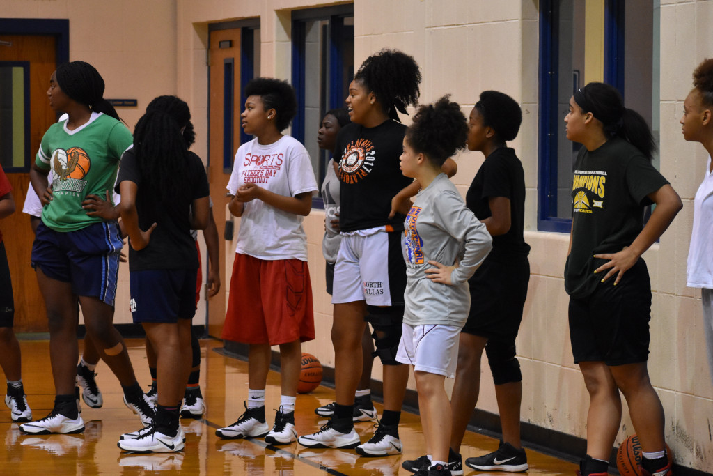 North Dallas High teammates Ashley Poole (left), SaNiya Lampkin and Terri Jeffery (back) wait on the next drill.
