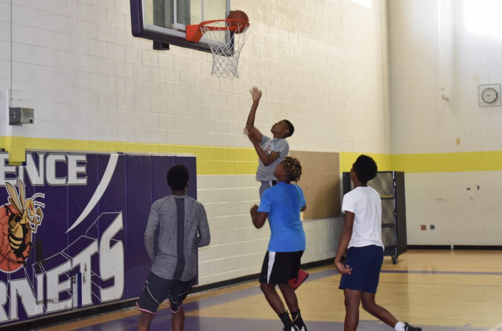 Chandler DeVeaux goes up for a layup as Terry Smith (left), Cinque Lampkin and Nathaniel Chambers follow on the play.