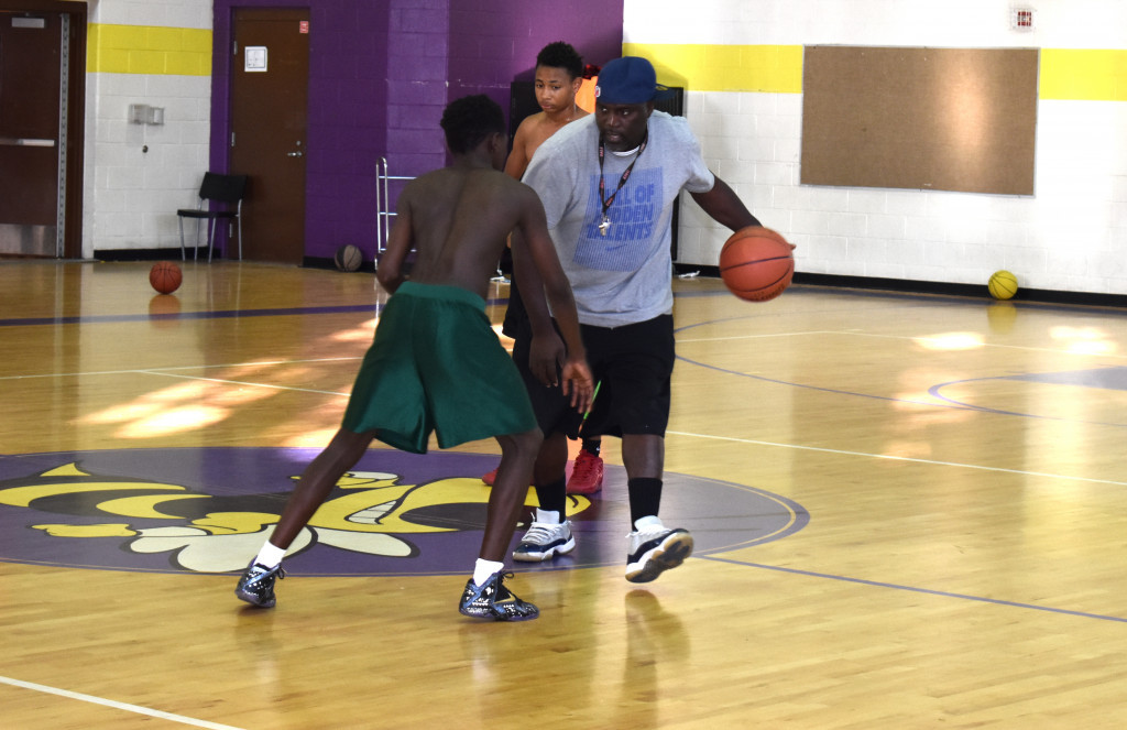 Coach Mickael Lampkin demonstrates how to protect the ball while dribbling.