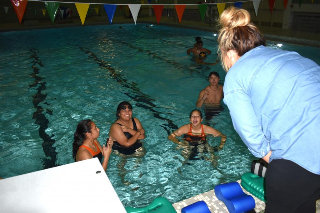 Coach Stephanie Page talks to Iliana Morfin, Melanie Martinez and Emily Arenas about what to do to improvetheir swimming.