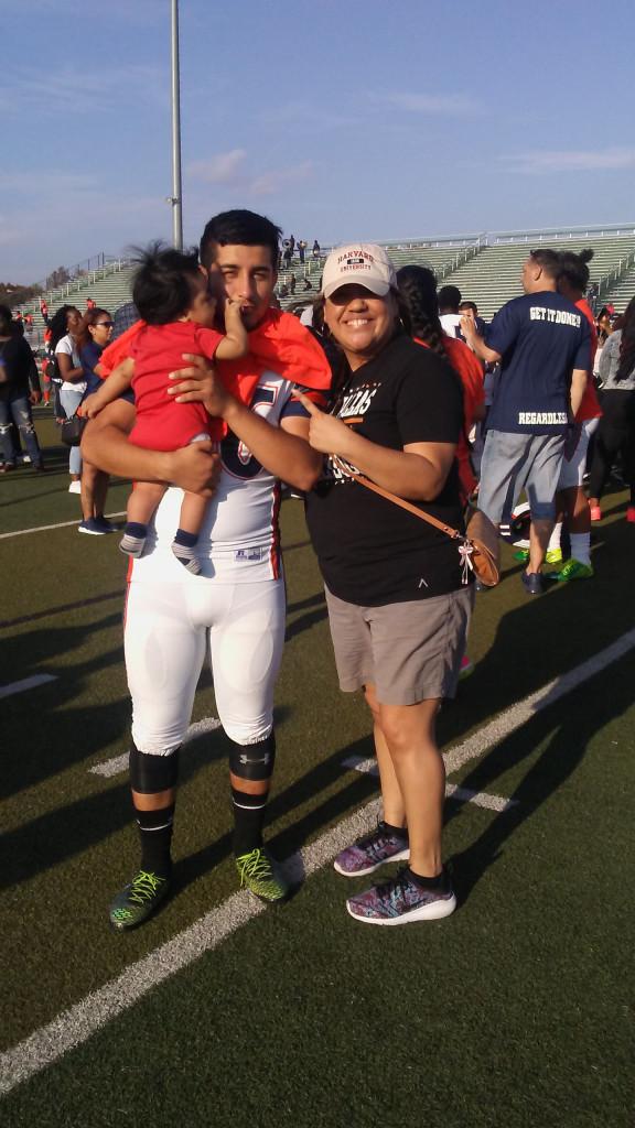 Juan Carpio, holding his nephew, visits with his former teacher Christina Herrera after a recent game.