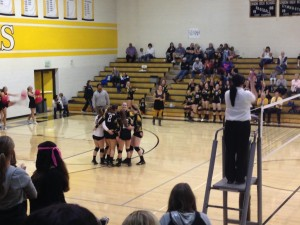 The volleyball girls coming together to celebrate a point.