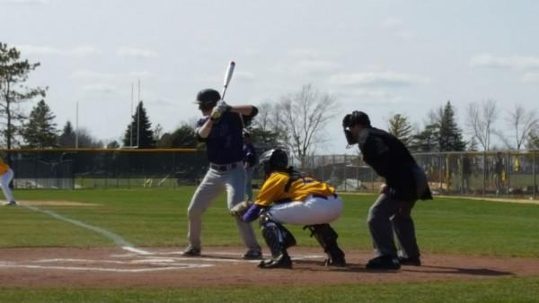 Former teammates, now opponents. Ryan Bernady bats as Noah Bluth catches.