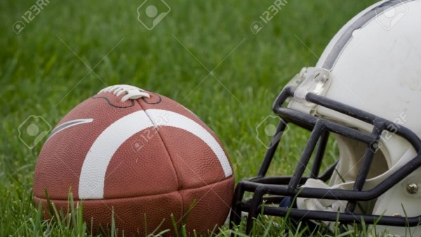 4029485-Photo-of-an-American-football-and-a-helmet-on-a-grass-field-horizontal--Stock-Photo