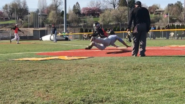 Aaron Zavala dives to the back corner of home plate, narrowly avoiding the catcher's tag on Ryan Brown's 2 RBI single.