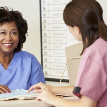 Two Female Nurses In Discussion Over Patients Notes At Nurses Station