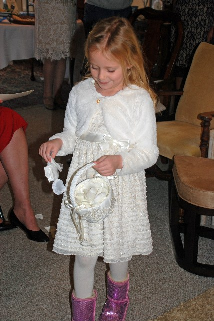 The flower girl, Olivia Stone, granddaughter of the bride, dropped  her rose petals from the dining room to the living room, site of the  ceremony.