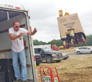 Delaware Alcohol and Tobacco Enforcement agent Jack Renaud heaves bottles of liquor to be crushed. (Photo credit: Delaware State News/Craig Anderson)