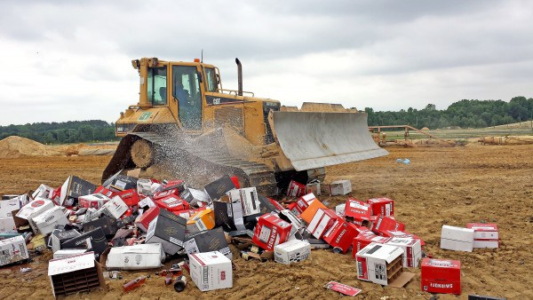 A bulldozer pulverizes a pile of confiscated liquor bottles and cans on Friday afternoon at the Central Solid Waste Management Center Sandtown landfill near Felton. (Photo credit: Delaware State News/Craig Anderson)
