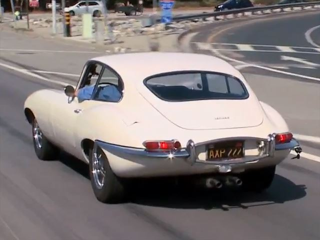 Jay Leno checks out a Jaguar XKE