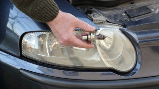 Broken H4 car light bulb in mechanic hand